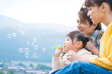 シャボン玉をする娘に寄りそう夫婦の写真素材 [FYI02646180]