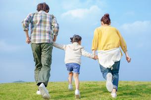 手をつなぎ走る家族の後ろ姿の写真素材 [FYI02646192]