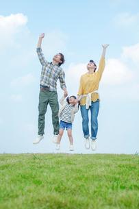 手をつなぎジャンプする親子の写真素材 [FYI02646206]