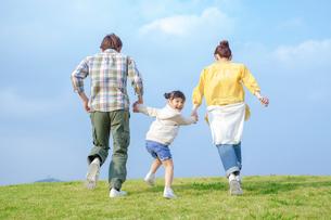 手をつなぎ走る家族の写真素材 [FYI02646326]