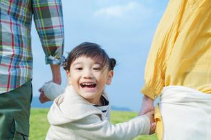 両親と手を握り振り向く女の子の写真素材 [FYI02646552]