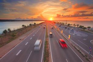 ロードパークの歩道橋上から望む本島側の海中道路と夕日の写真素材 [FYI02646784]