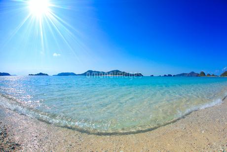 阿真ビーチの渚と嘉比島など慶良間諸島と太陽の光芒の写真素材 [FYI02648395]