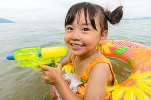 海で水鉄砲で遊ぶ水着の子供の写真素材 [FYI02648613]