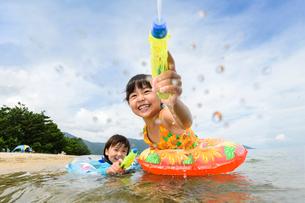 海で水鉄砲で遊ぶ水着の子供の写真素材 [FYI02648729]