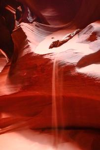 赤味を帯びた地層から砂が流れ落ちるアンテロープ・キャニオンの写真素材 [FYI02648738]