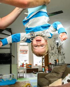お父さんに逆さまに抱き上げられる男の子の写真素材 [FYI02648778]