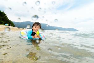 海で水鉄砲で遊ぶ水着の子供の写真素材 [FYI02648923]