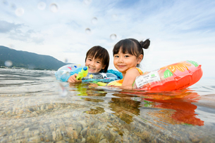 海で水鉄砲で遊ぶ水着の子供の写真素材 [FYI02648965]