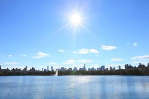 太陽に輝くセントラルパーク貯水池と雲とスカイラインの写真素材 [FYI02649011]