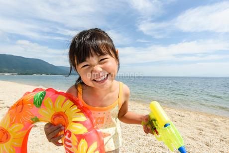 浮き輪と水鉄砲を持って遊ぶ女の子の写真素材 [FYI02649028]