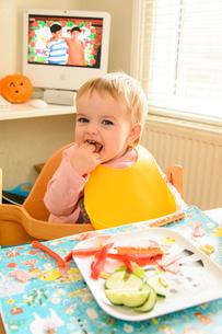 椅子に座って野菜を食べる赤ちゃんの写真素材 [FYI02649036]