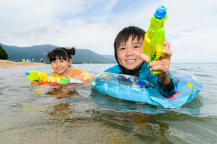 海で水鉄砲で遊ぶ水着の子供の写真素材 [FYI02649081]