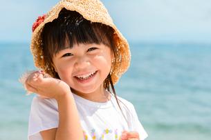 貝殻を耳に当てる女の子の写真素材 [FYI02649208]