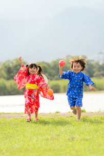 芝生を走る浴衣の子供の写真素材 [FYI02649269]