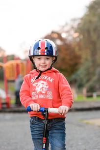 公園でスクーターに乗って遊ぶ男の子の写真素材 [FYI02649275]