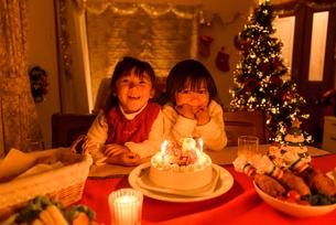 クリスマスケーキの前で並んで座る女の子の写真素材 [FYI02649283]