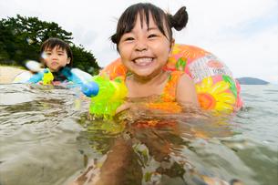 海で水鉄砲で遊ぶ水着の子供の写真素材 [FYI02649285]