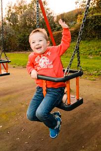 公園のブランコに乗って遊ぶ男の子の写真素材 [FYI02649296]