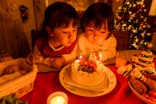 クリスマスケーキの前で並んで座る女の子の写真素材 [FYI02649297]