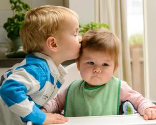 赤ちゃんの頭にキスする男の子の写真素材 [FYI02649319]