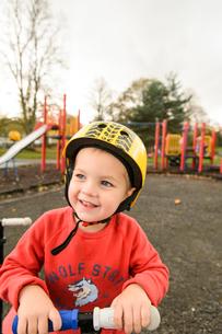 公園でスクーターに乗って遊ぶ男の子の写真素材 [FYI02649352]