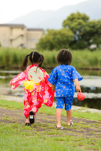 手をつないで歩く後ろ姿の浴衣の子供の写真素材 [FYI02649404]