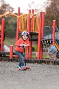 公園でスクーターに乗って遊ぶ男の子の写真素材 [FYI02649464]