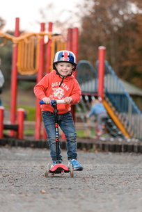 公園でスクーターに乗って遊ぶ男の子の写真素材 [FYI02649499]