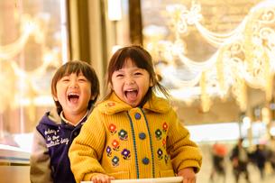 クリスマスで飾ったショウウインドーの前に立つ女の子と男の子の写真素材 [FYI02649538]