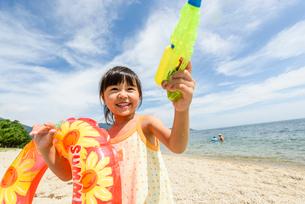 浮き輪と水鉄砲を持って遊ぶ女の子の写真素材 [FYI02649545]