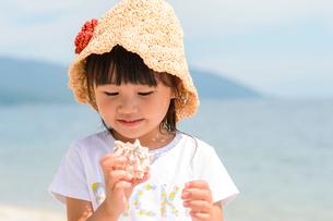 貝殻を見つめる女の子の写真素材 [FYI02649578]