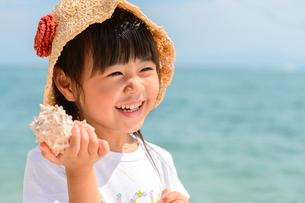 貝殻を耳に当てる女の子の写真素材 [FYI02649725]