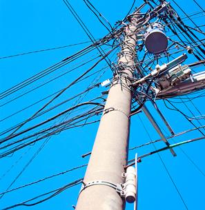 錯綜する電線をつるす電柱の写真素材 [FYI02649819]