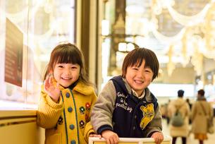 クリスマスで飾ったショウウインドーの前に立つ女の子と男の子の写真素材 [FYI02649849]