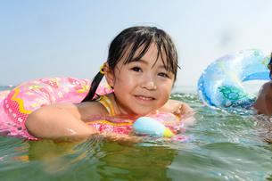 浮き輪につかまって水鉄砲で遊ぶ女の子の写真素材 [FYI02649925]