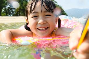 浮き輪につかまって水鉄砲で遊ぶ女の子の写真素材 [FYI02649970]