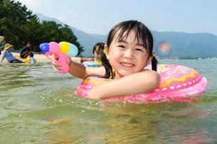 浮き輪につかまって水鉄砲で遊ぶ女の子の写真素材 [FYI02650062]