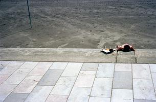 サーフボードを横にして眠るサーファーの写真素材 [FYI02650366]