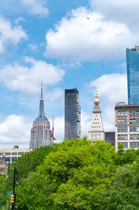 新緑生い茂るユニオンスクエアパークとエンパイヤーと高層ビル群を覆う雲の写真素材 [FYI02650385]
