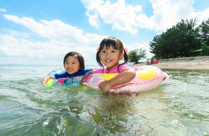 浮き輪を使って泳ぐ男の子と女の子の写真素材 [FYI02650398]