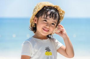 貝殻を耳に当てる女の子の写真素材 [FYI02650615]