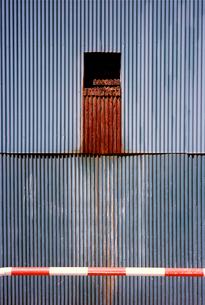 波形トタン壁と紅白の車避け支柱の写真素材 [FYI02650776]
