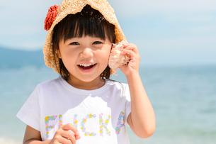 貝殻を耳に当てる女の子の写真素材 [FYI02650862]