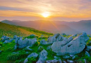 四国カルスト姫鶴牧場の石灰岩群と妙見森方向の山並みと夕日の写真素材 [FYI02650884]