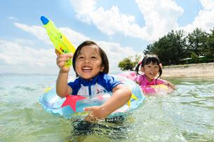 水鉄砲を持って浮き輪で泳ぐ男の子と女の子の写真素材 [FYI02651005]