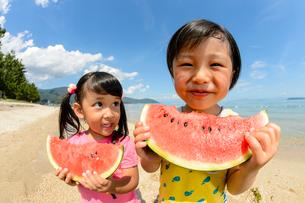 並んでスイカを食べる男の子と女の子の写真素材 [FYI02651026]