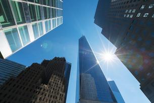 ダウンタウンビル群とワンワールドトレードセンターの間で輝く太陽の写真素材 [FYI02651193]