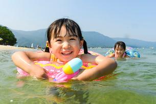 浮き輪につかまって水鉄砲で遊ぶ女の子の写真素材 [FYI02651237]