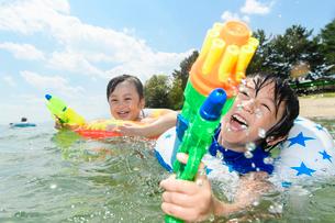 水鉄砲で遊ぶ男の子と女の子の写真素材 [FYI02651257]